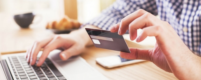 person typing credit card details with laptop