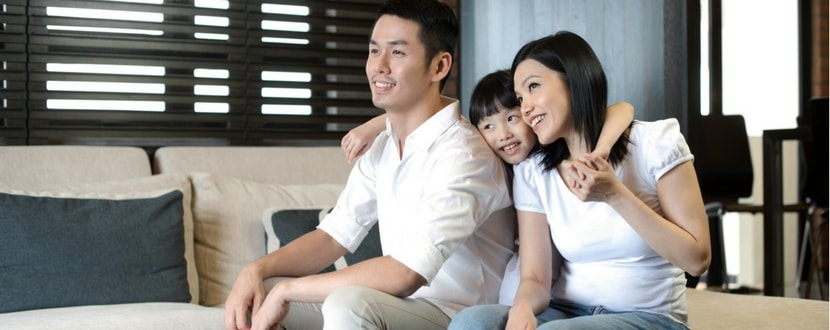 Young family sitting on couch-min
