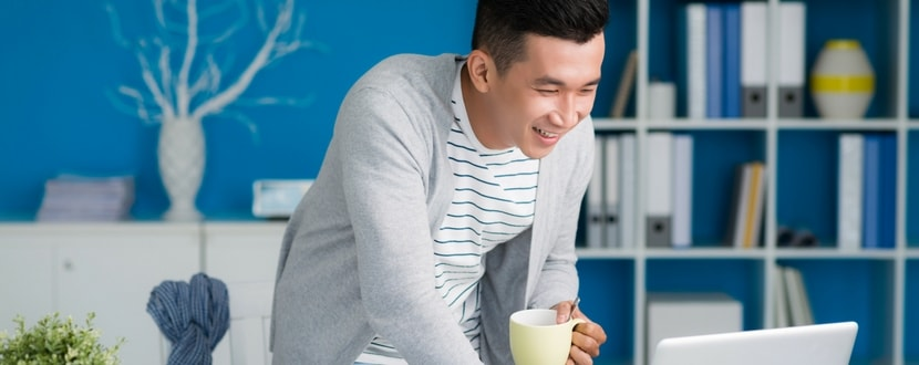man smiling with laptop and cup - SingSaver