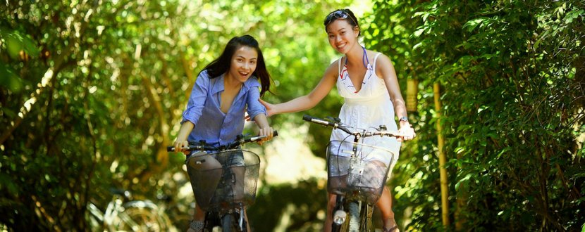 two woman cycling in nature - SingSaver