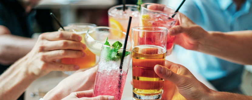 Group of friends toasting to alcoholic drinks - SingSaver