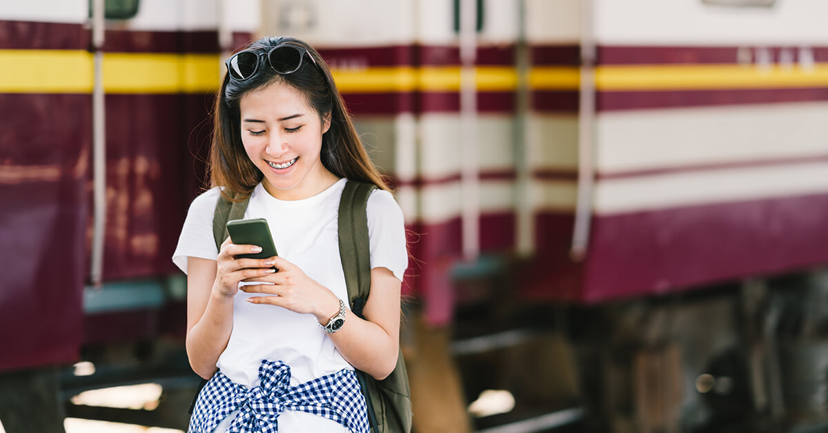 Lady looking at her phone in front of a train - SingSaver
