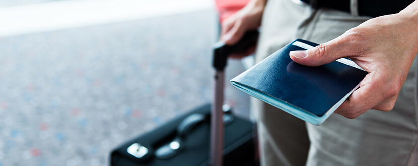 man carrying luggage and passport in airport -SingSaver
