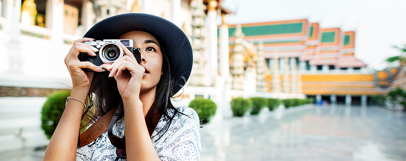 girl travelling and snapping pictures with camera | SingSaver