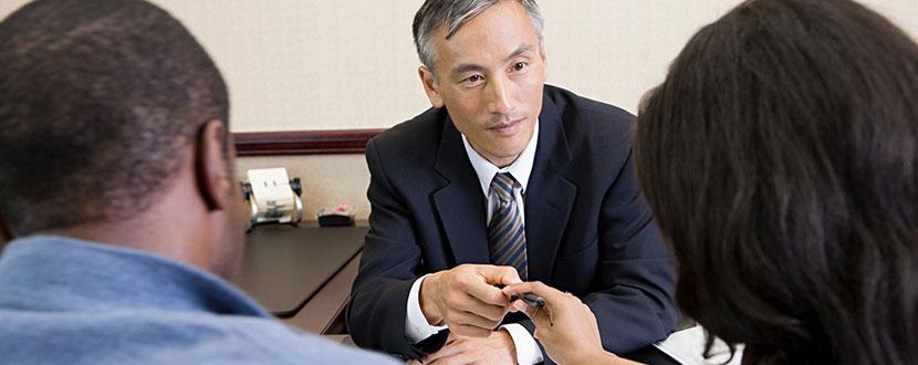 agent handing over a pen to client -SingSaver