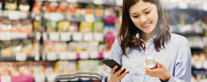 lady using mobile phone while grocery shopping -SingSaver
