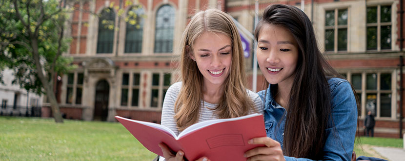 2 female university students looking at university guide book -SingSaver