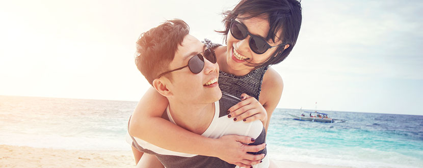 couple enjoying themselves on a beach -SingSaver