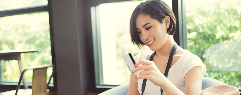 girl smiling with a credit card in hand -SingSaver