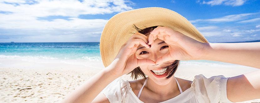Lady on a beach making a heart shape -SingSaver