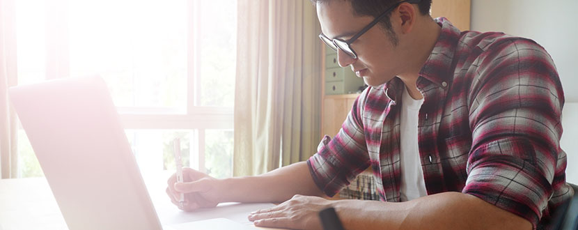 Guy in front of a laptop and writing notes - SingSaver
