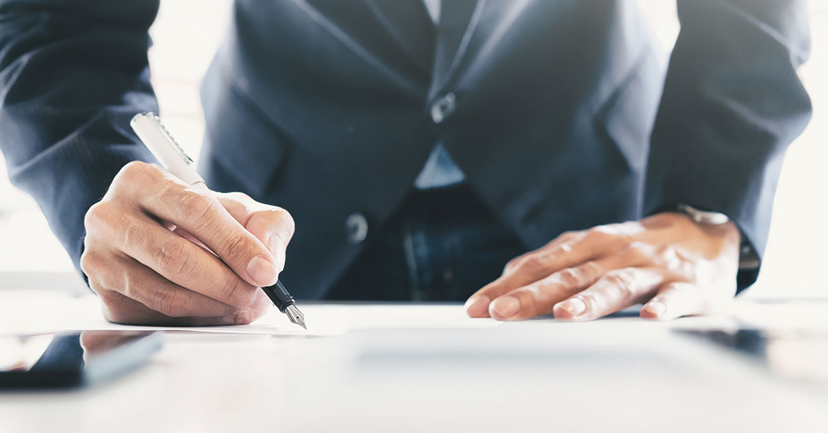 Man signing a document using an ink pen - SingSaver